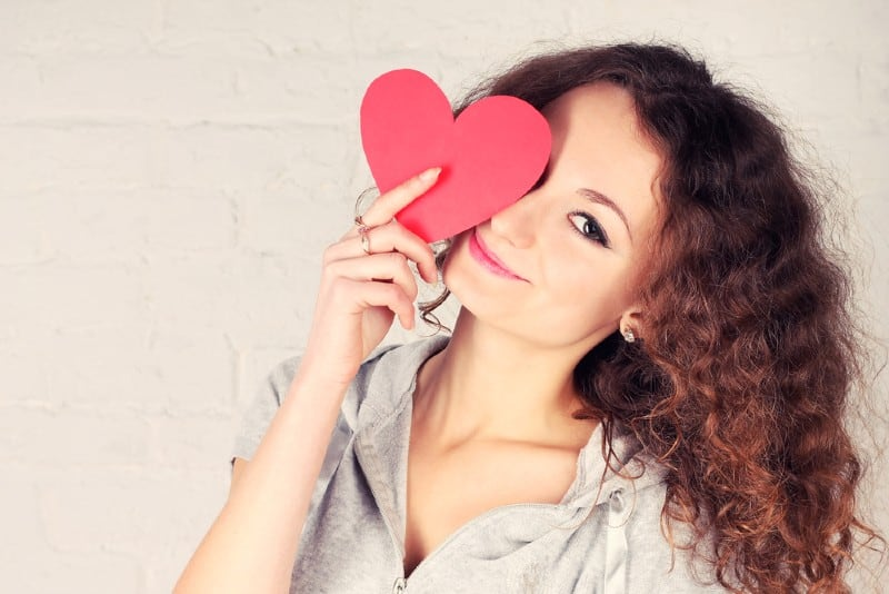 une femme tenant un coeur de papier rouge devant l'un de ses yeux