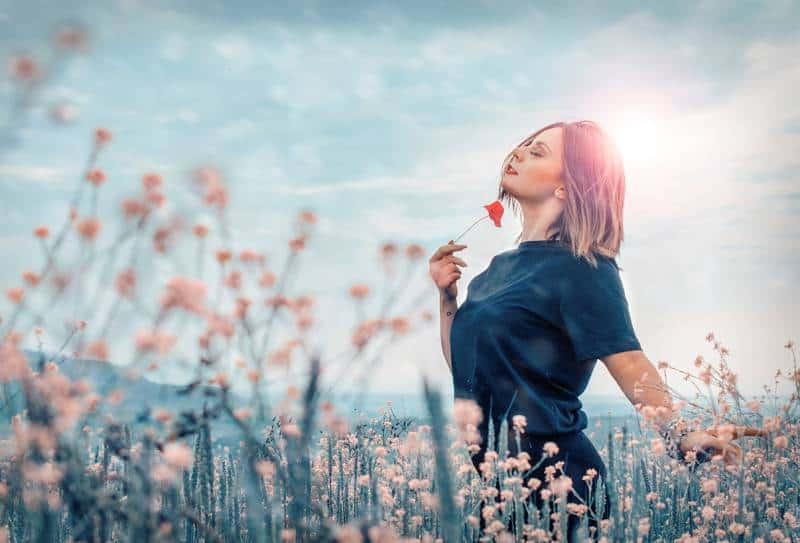 femme tenant une fleur rouge