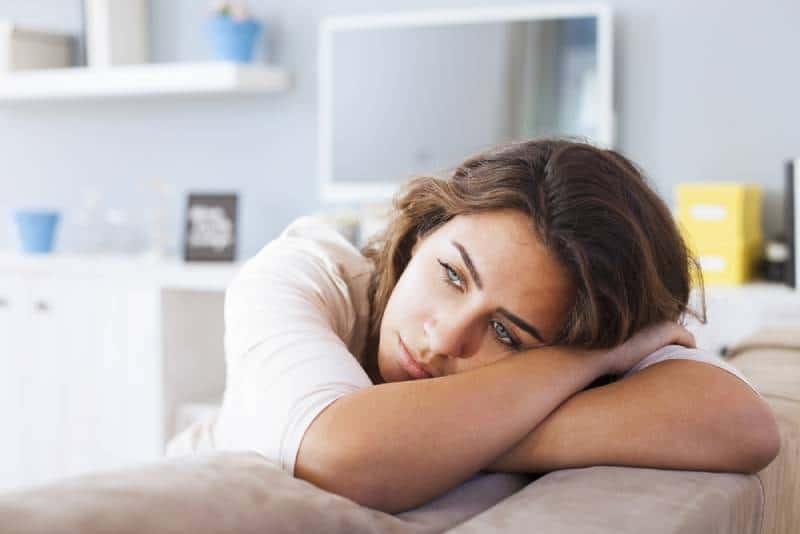 femme triste allongée sur le canapé et pensant