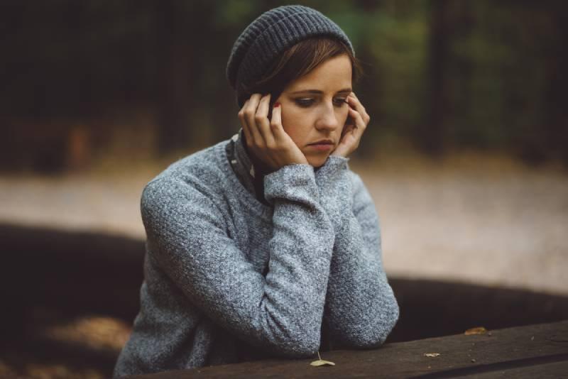 femme triste assise seule dans la forêt