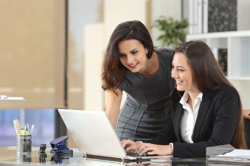 deux femmes travaillant ensemble avec un ordinateur portable sur un bureau dans le bureau