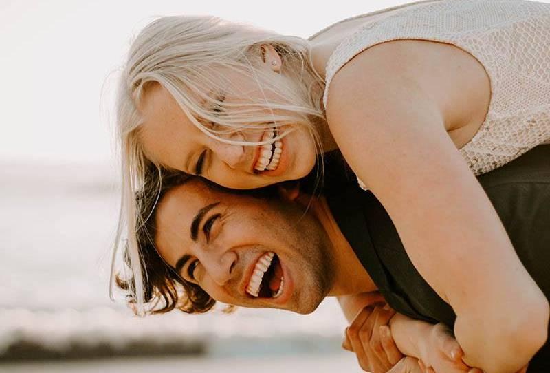 gros plan sur la photo d'un homme souriant portant une femme blonde heureuse à l'extérieur