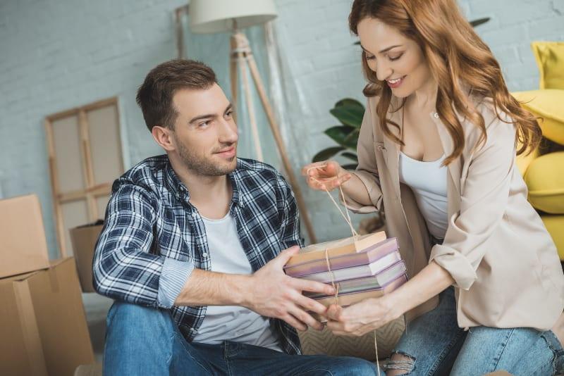 homme aidant une femme souriante avec ses livres