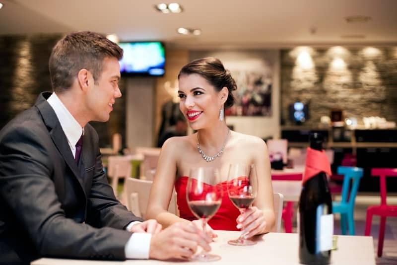 un homme et une femme boivent du vin rouge à une table dans un restaurant