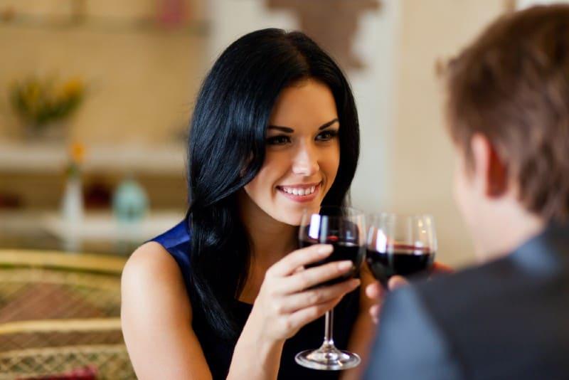 Un homme et une femme buvant du vin rouge assis l'un en face de l'autre à une table
