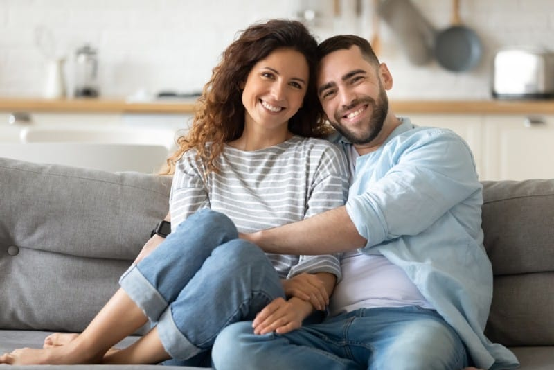un homme heureux et une femme assise sur le canapé se serrant