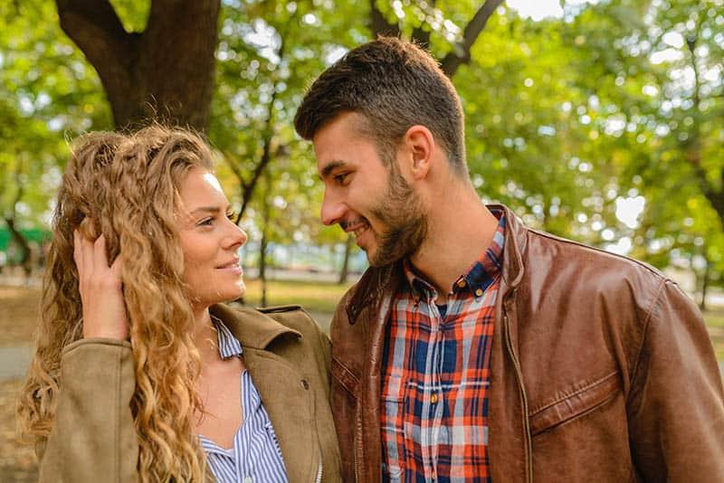 homme et femme souriants se regardent les yeux