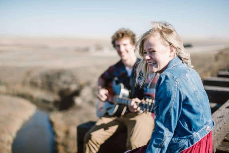homme jouant de la guitare à côté d'une fille souriante