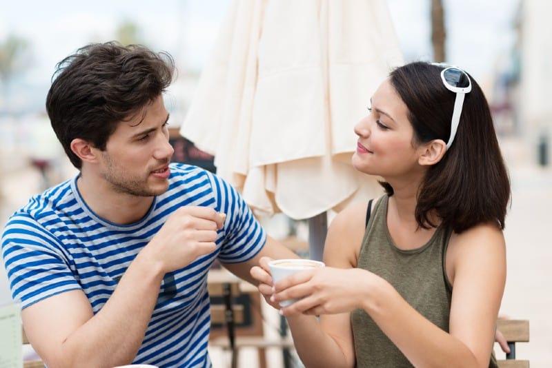 un homme parle à une femme qui est assise à côté de lui à une table et boit du café