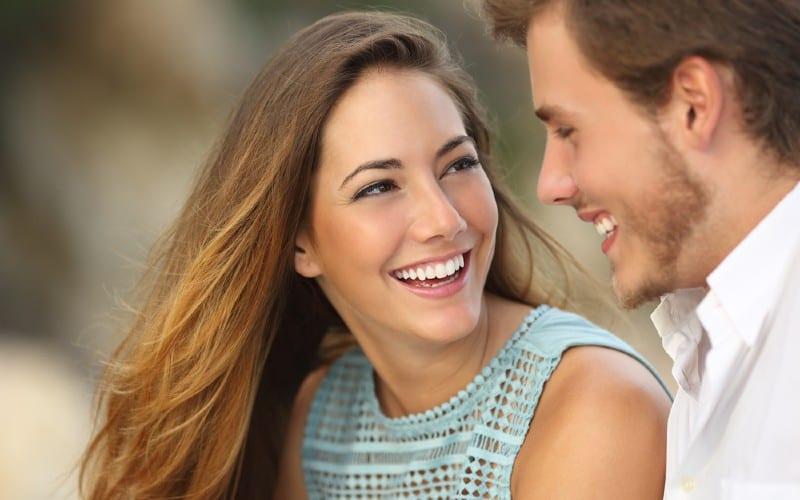 homme souriant regarde dans les yeux de femme heureuse