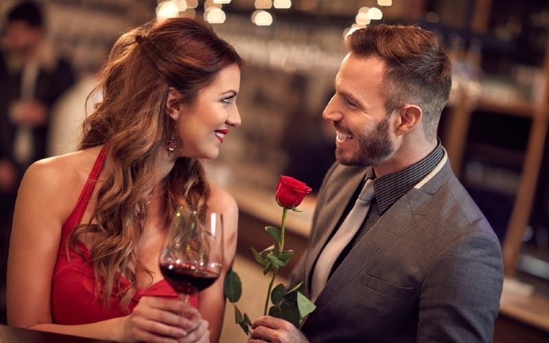 homme souriant donnant rose a femme