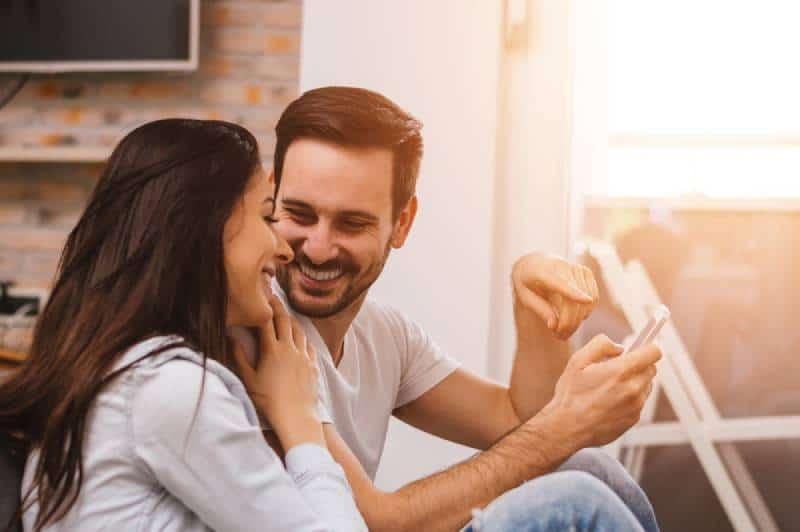 homme tenant le téléphone tout en souriant femme le regardant