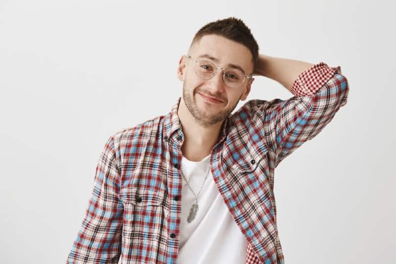 homme timide portant des lunettes debout près d'un mur blanc