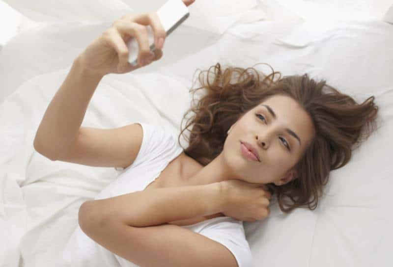 jeune brune allongée sur le lit et regardant son téléphone