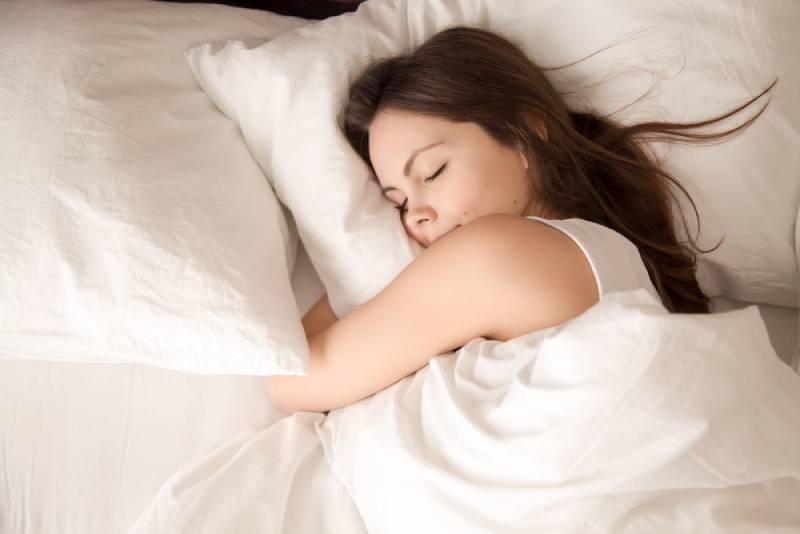 jeune femme dormant bien dans son lit et étreignant un oreiller blanc et doux