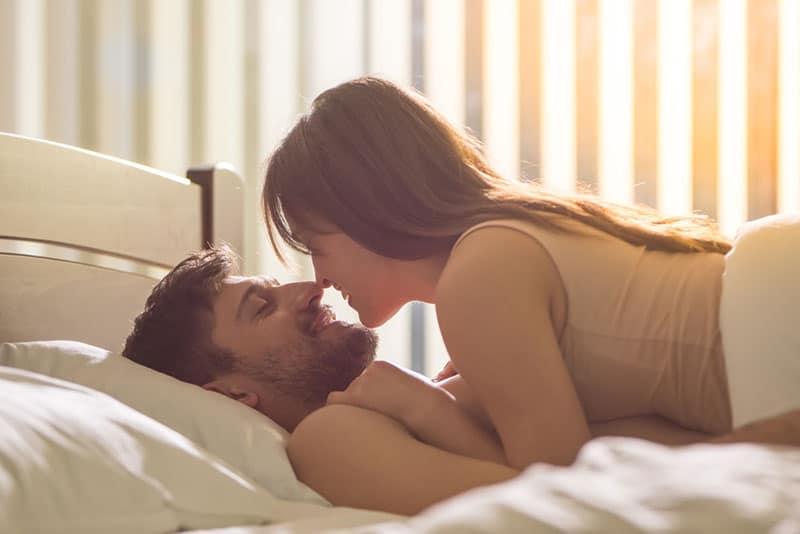 joli couple allongé sur le lit et se regardant