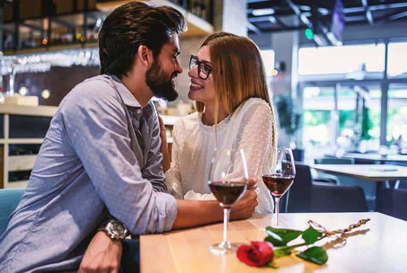 joli couple assis l'un à côté de l'autre dans un café