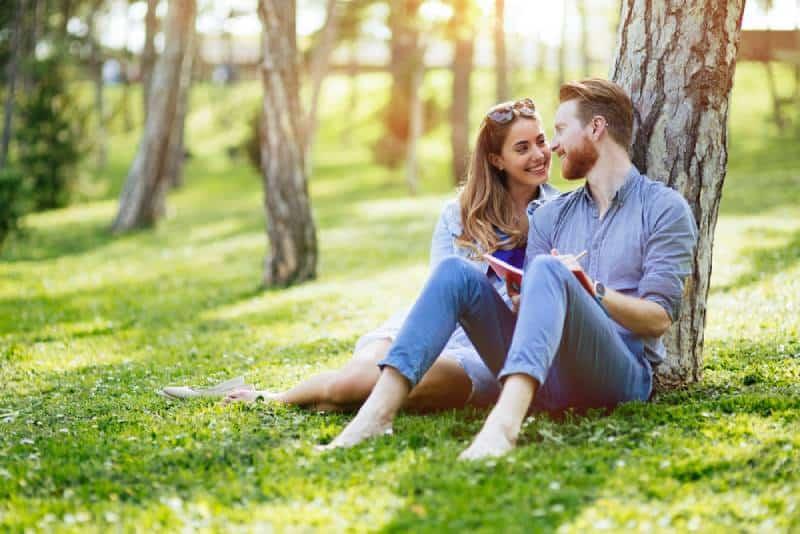 joli couple assis sur l'herbe et appuyé sur un arbre