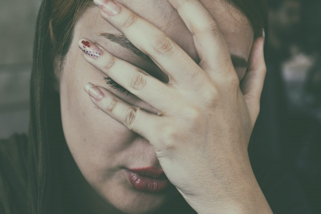 la femme a couvert son visage avec sa main