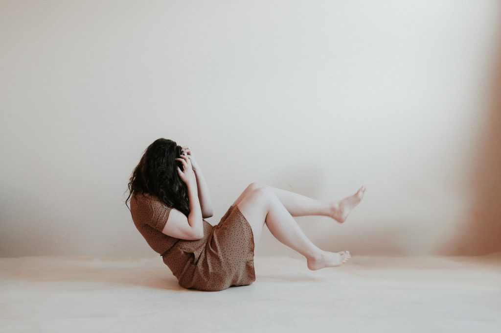 la femme est assise par terre et tient sa tête