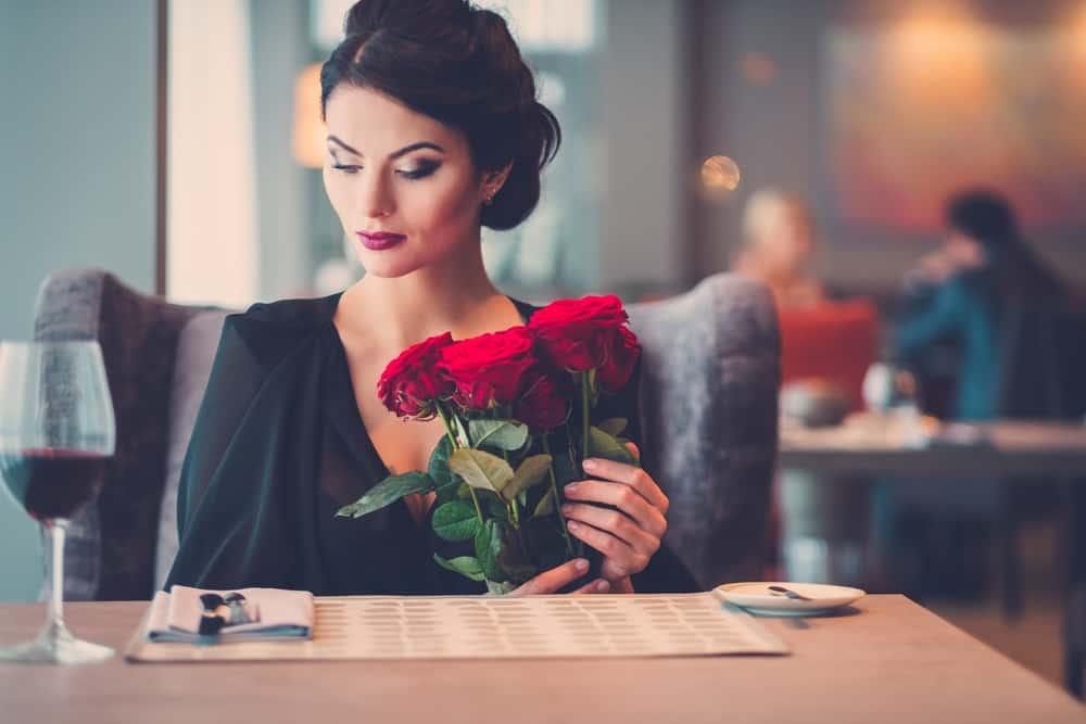 la femme est assise seule avec un bouquet de roses à la main