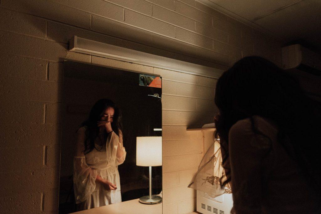 la femme pleure à côté du miroir