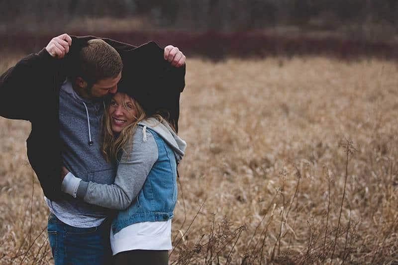 l'homme protège la femme de la pluie avec sa veste