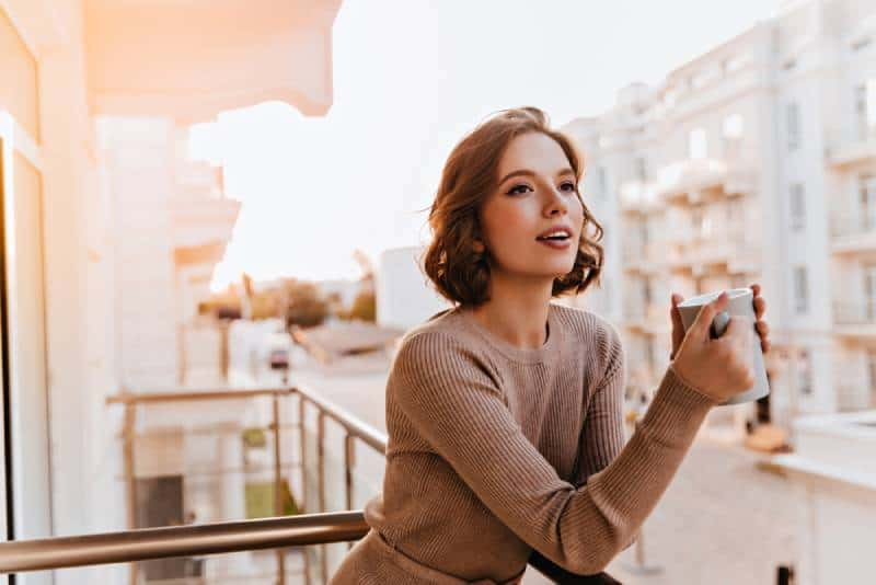 modèle féminin tenant une tasse de café