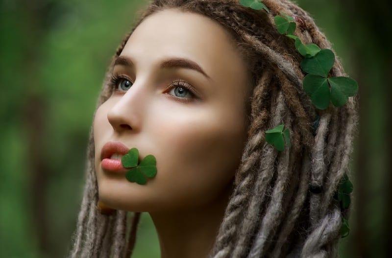 un portrait d'une belle femme avec des trèfles dans les cheveux et la bouche
