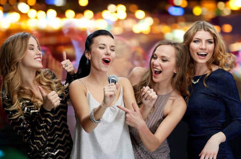 trois femmes en robe du soir avec micro chantant le karaoké