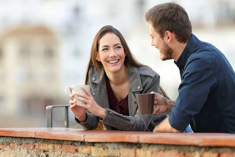 un couple heureux qui parle dehors et boit du café