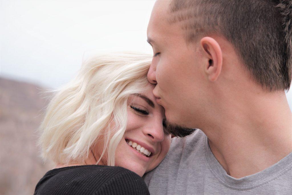 un homme embrasse une femme et l'embrasse sur le front