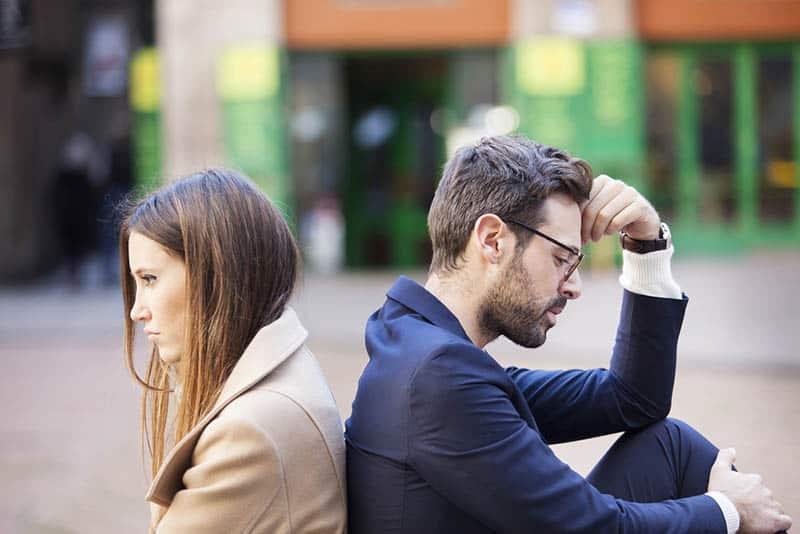 un homme et une femme bouleversés, assis dehors dos à dos