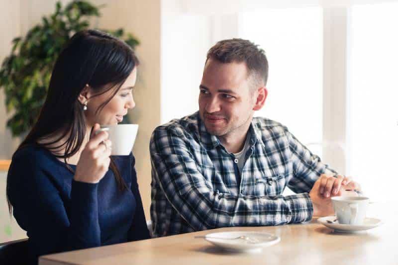 un homme et une femme discutant au café et buvant du thé