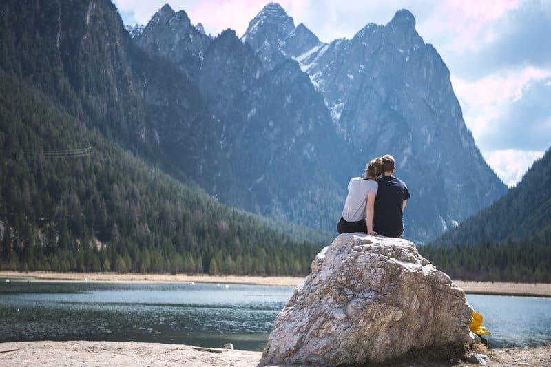 un homme et une femme embrassant sur un rocher
