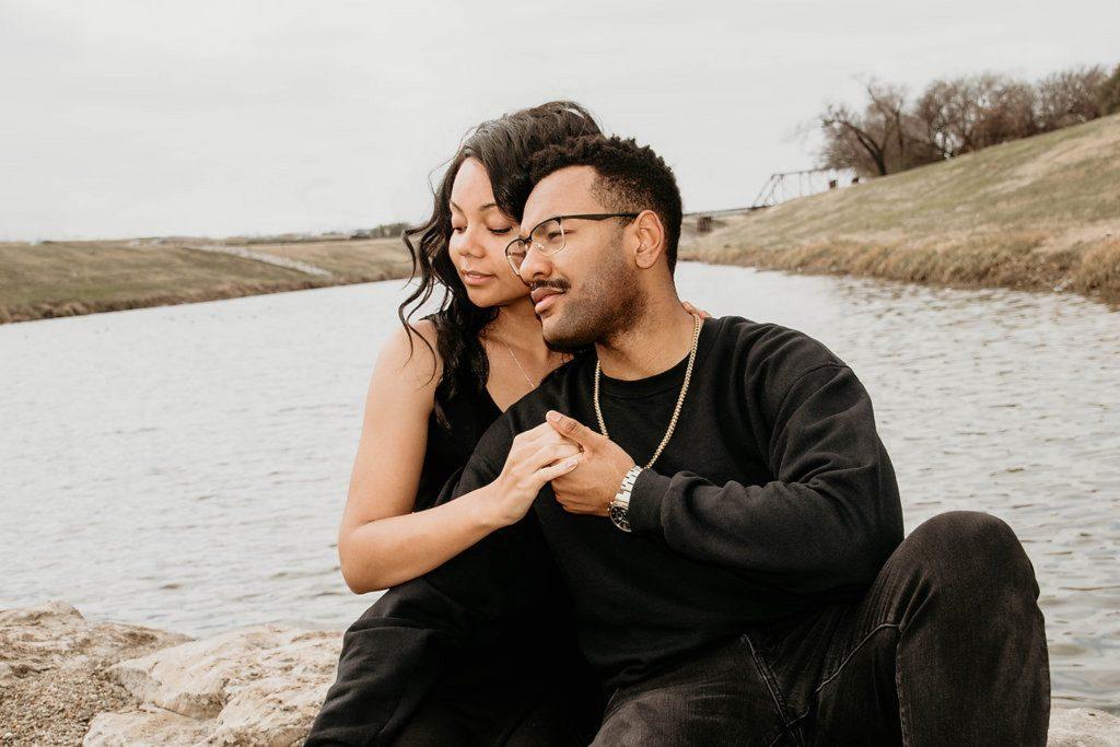 un homme et une femme s'asseyent au bord de la rivière