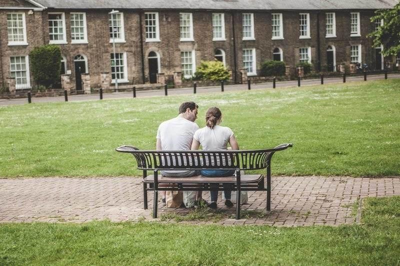 un homme et une femme sont assis sur un banc, le dos tourné