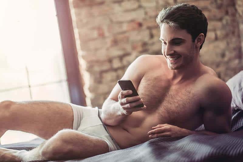 un homme qui tape sur son téléphone à la maison
