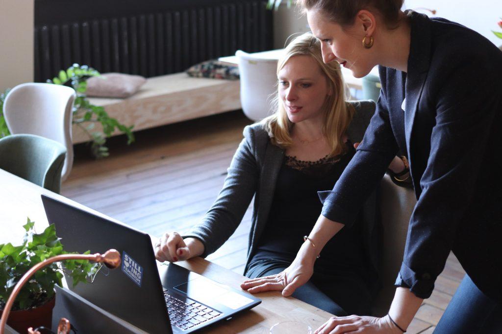 une femme assise avec un ami devant un ordinateur portable