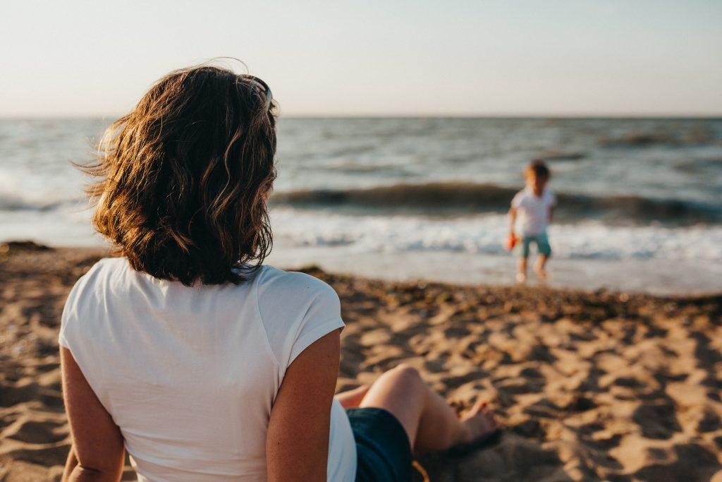 une femme assise sur la plage un enfant joue