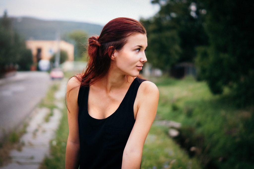 une femme aux cheveux rouges détourne le regard