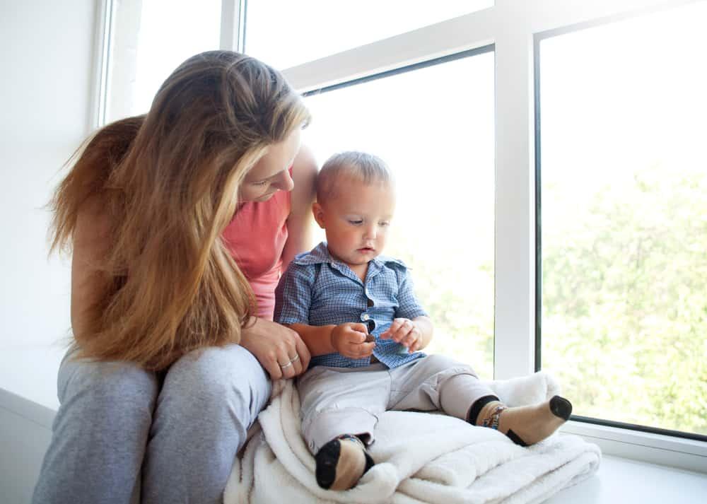 une femme avec son fils est assise et joue
