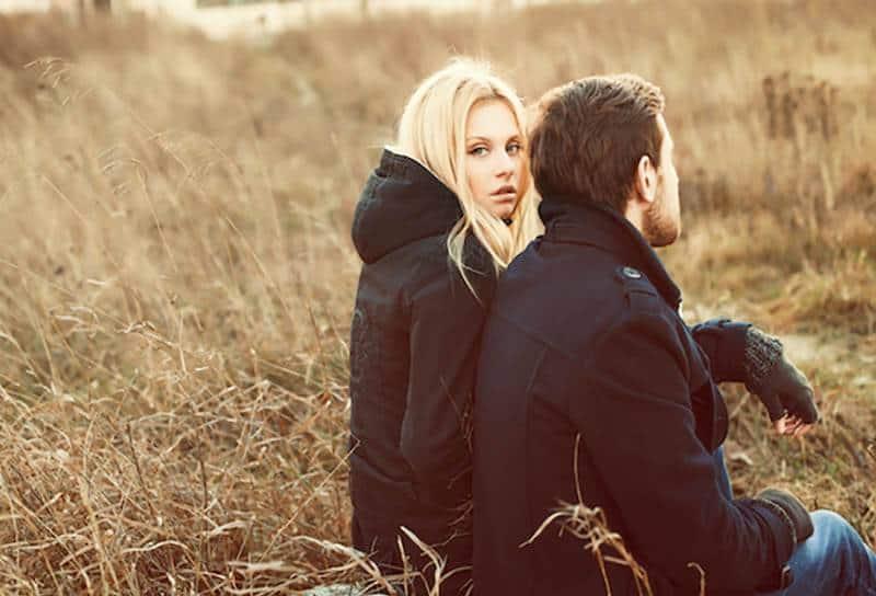 une femme blonde attentionnée assise à côté d'un homme portant une veste noire et des gants à l'extérieur