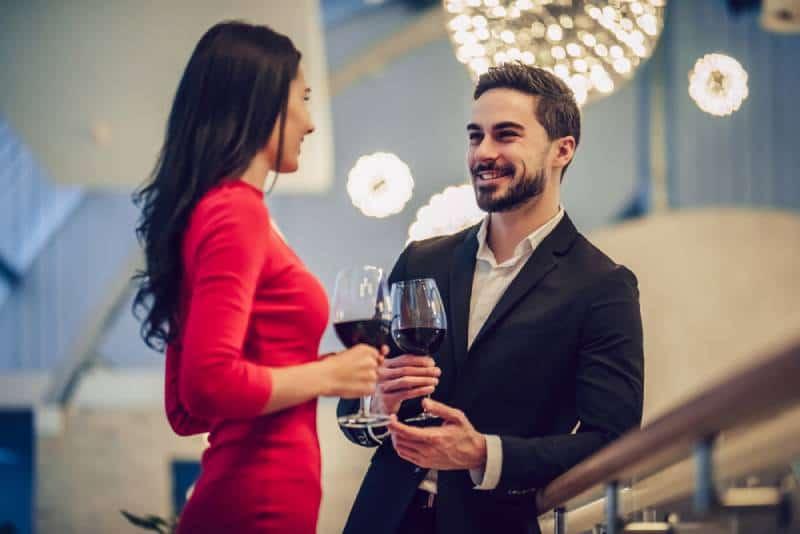 une femme en robe rouge et un bel homme en costume discutant avec un verre de vin