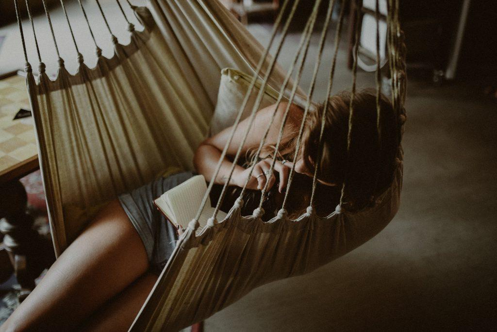une femme est assise sur une chaise longue et lit un livre