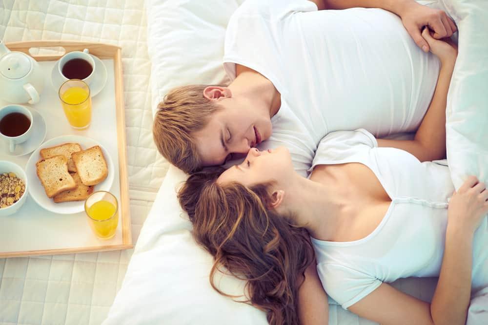 une femme et un homme se trouvent dans son lit