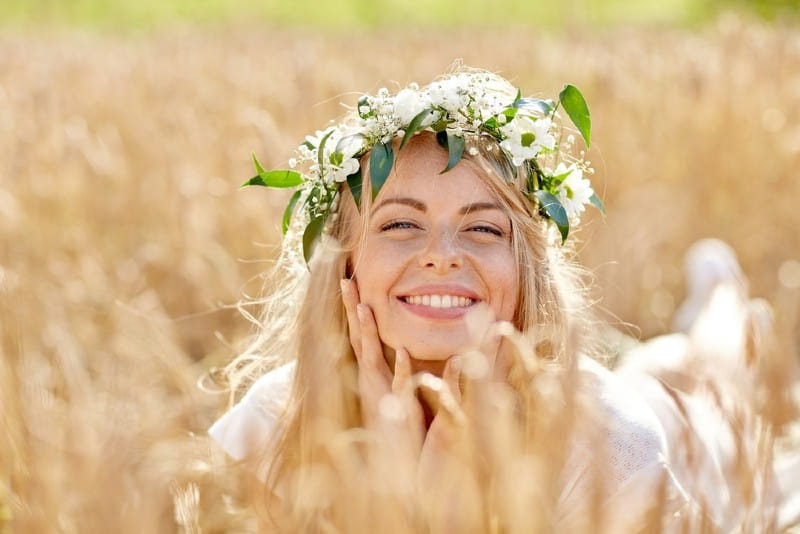 une femme heureuse allongée sur un champ portant une couronne de fleurs