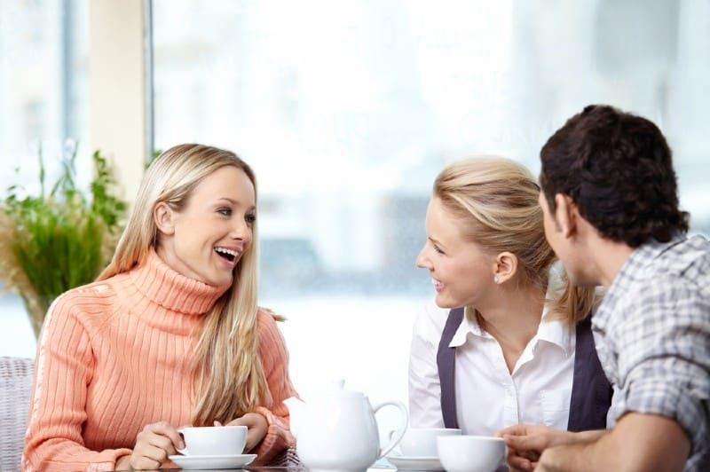 une femme heureuse parle à un homme et une femme