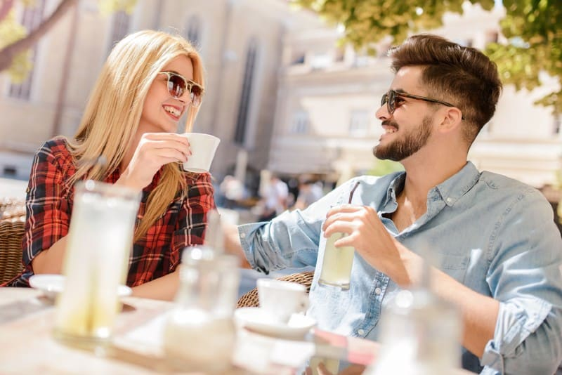 une femme parlant à l'homme sur une séance de café à une table en plein air
