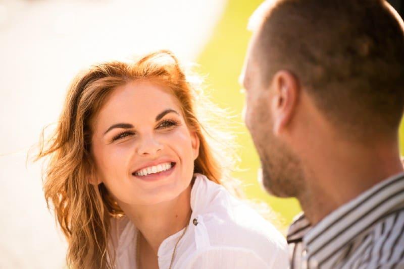 une femme souriante écoutant un homme qui est assis devant elle
